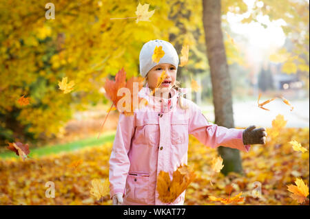 Cute little girl with missing teeth playing with yellow fallen leaves in autumn forest, trowing into the air. Happy child laughing and smiling. Sunny - Stock Photo