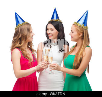 three women wearing hats with champagne glasses - Stock Photo