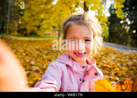 Cute little girl with missing teeth taking selfie. Happy child laughing and smiling. Sunny autumn forest, sun beam. - Stock Photo