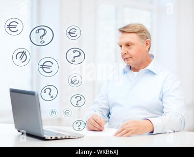 old man with laptop filling a form at home - Stock Photo