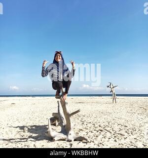 Teenage Girl Gesturing Peace Sign While Sitting On Driftwood At Beach Against Blue Sky - Stock Photo