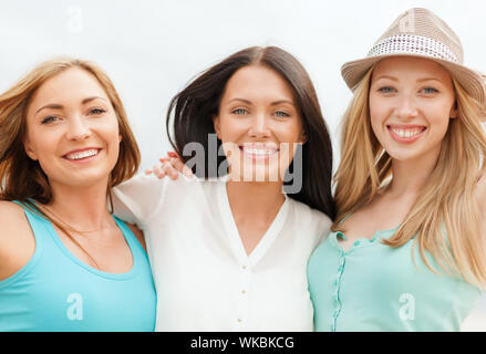 group of smiling girls chilling on the beach - Stock Photo