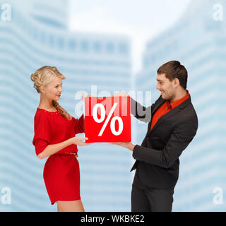shopping, sale, christmas, couple and x-mas concept - smiling woman and man with red percent sale sign outdoors - Stock Photo