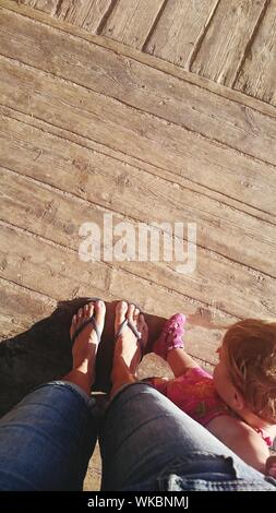 Low Section Of Mother Standing With Baby Girl On Wooden Boardwalk - Stock Photo