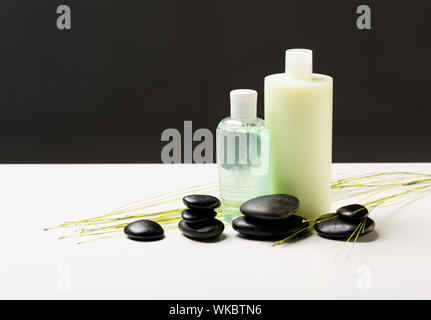 spa, health and beauty concept - closeup of shampoo bottle, massage stones and green plant - Stock Photo