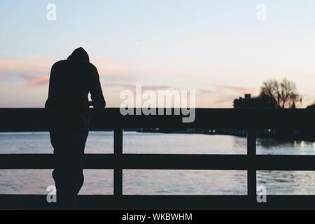 Rear View Of Silhouette Man Standing On Pier Over Sea - Stock Photo