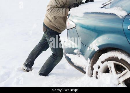 closeup of man pushing car stuck in snow - Stock Photo