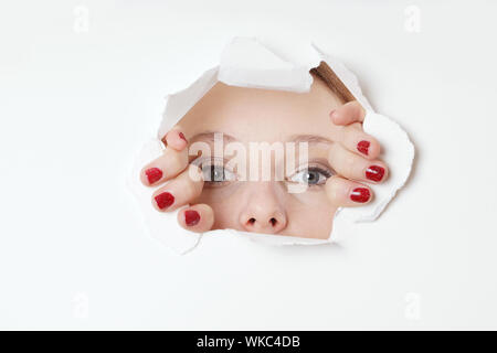 Portrait Of Woman Looking Through Torn Paper