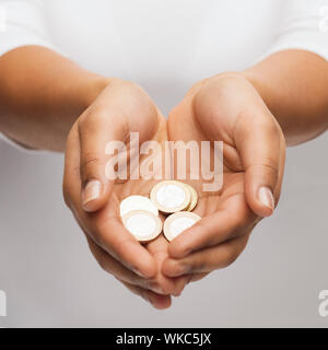 womans cupped hands showing euro coins - Stock Photo