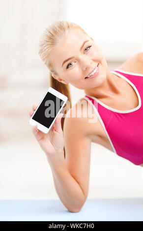 fitness, technology, advertiding and exercise concept - smiling woman lying on the floor and sowing smartphone blank black screen - Stock Photo