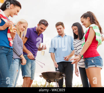 summer, holidays, vacation, happy people concept - group of friends having picnic and making barbecue on the beach - Stock Photo