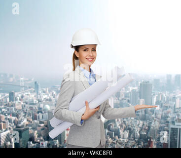 building, developing, consrtuction and architecture concept - smiling architect in helmet with blueprints showing something on palm of hand - Stock Photo
