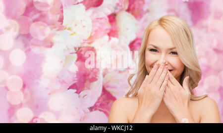 beautiful woman covering her mouth - Stock Photo