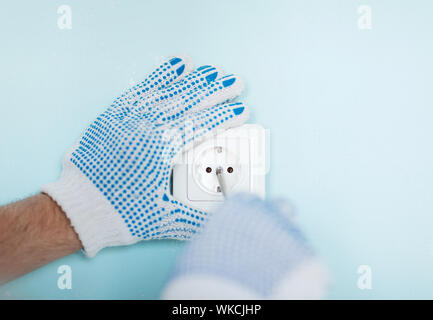 close up of male in gloves installing new socket - Stock Photo