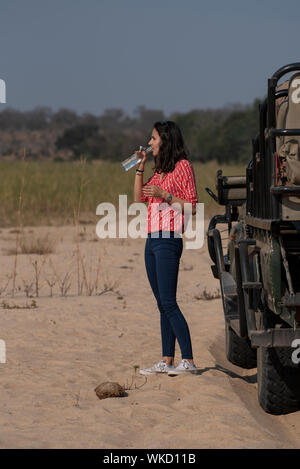 Tourist drinking water on safari - Stock Photo