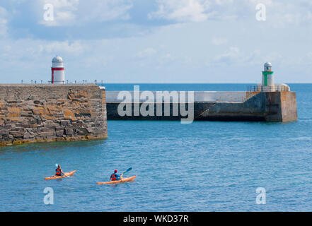 Sea kayakers paddling past the entrance to Laxey Harbour, Isle of Man - Stock Photo