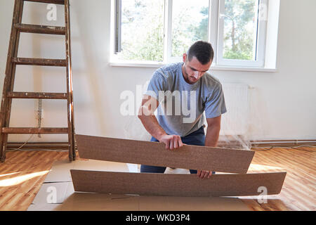 Handyman at the parquet laying at renovation in a new apartment - Stock Photo