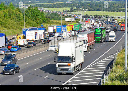 View from above of motorway countryside landscape with traffic jam on M25 & busy lorry truck movement on near side four lane section Essex England UK - Stock Photo