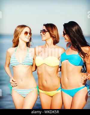 girls in bikinis walking on the beach - Stock Photo