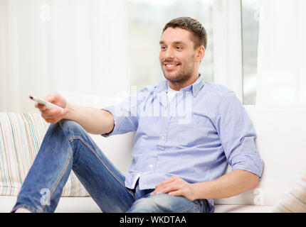 home, technology and entretainment concept - smiling man with tv remote control at home - Stock Photo