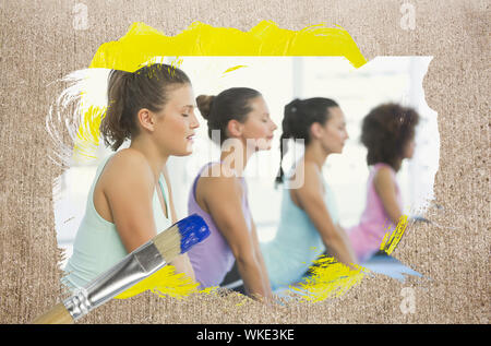 Composite image of yoga class in the gym against weathered surface with paintbrush - Stock Photo