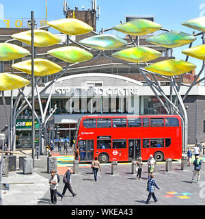Stratford East London shoal titanium fish sculpture outside old shopping centre red double decker Stagecoach public transport bus  Newham England UK - Stock Photo