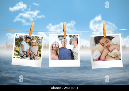 Composite image of instant photos hanging on a line against ocean and cityscape - Stock Photo