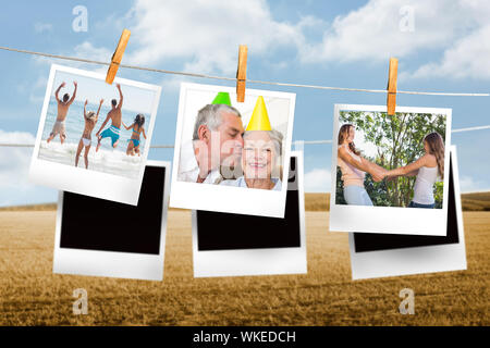 Composite image of instant photos hanging on a line against field and blue sky - Stock Photo