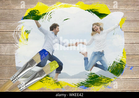 Composite image of couple jumping on the beach with paintbrush dipped in yellow against wooden surface with planks - Stock Photo
