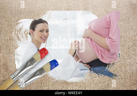 Composite image of pregnant woman at check up with doctor with paintbrush dipped in blue against weathered surface - Stock Photo