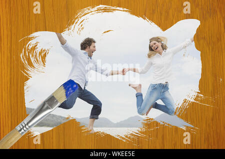 Composite image of couple jumping on the beach with paintbrush dipped in blue against wooden pine table - Stock Photo