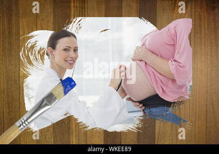 Composite image of pregnant woman at check up with doctor with paintbrush dipped in blue against wooden surface with planks - Stock Photo