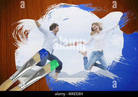 Composite image of couple jumping on the beach with paintbrush dipped in green against wooden oak table - Stock Photo