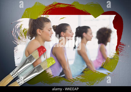 Composite image of yoga class in the gym with paintbrush dipped in yellow against digitally generated grey vignette background - Stock Photo
