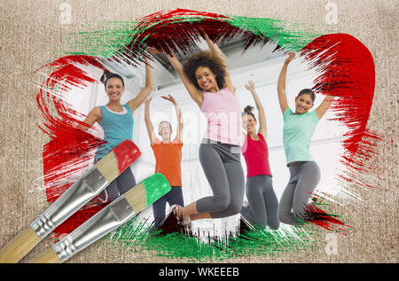 Composite image of fitness class at the gym with paintbrush dipped in green against weathered surface - Stock Photo