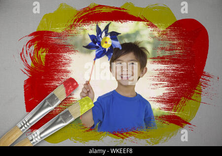 Composite image of little boy with pinwheel with paintbrush dipped in yellow against digitally generated grey background - Stock Photo