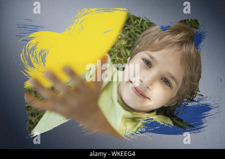 Composite image of little boy smiling at camera with blue paint against digitally generated grey vignette background - Stock Photo
