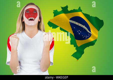 Excited japan fan in face paint cheering against green brazil outline with flag - Stock Photo