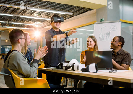 Young Chinese man wearing VR goggles watched by multiracial colleagues in an modern office - Stock Photo