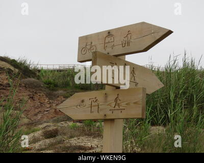 Low Angle View Of Arrow Sign Board On Beach Against Clear Sky - Stock Photo