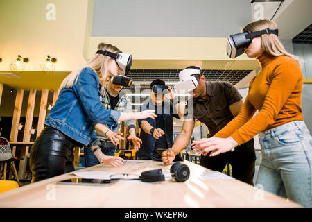 Business people using virtual reality goggles during meeting. Team of multiethnical developers testing virtual reality headset and discussing new