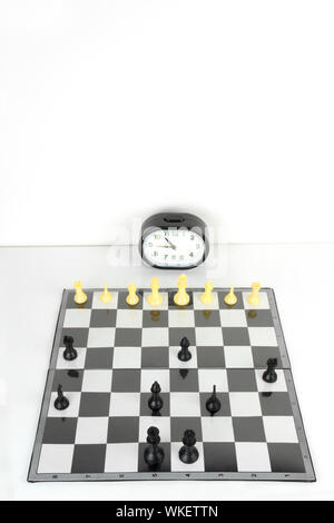 Chess board and timer set up on table - Stock Photo