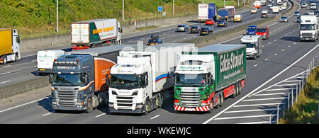 Supply chain hgv lorry truck drivers in cabs of articulated trailer vehicles overtaking in traffic lorries trucks busy four lane motorway England UK - Stock Photo