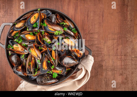 Marinara mussels, moules mariniere, in a large cooking pan, overhead shot on a dark rustic wooden background - Stock Photo
