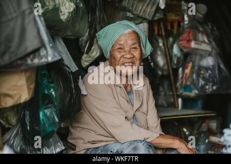 Phan Thiet, Vietnam - November 4, 2016: An unidentified vietnamese lady sitting at her shop in Phan Thiet, Vietnam. - Stock Photo