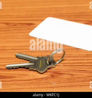 business card and keys on wood background - Stock Photo