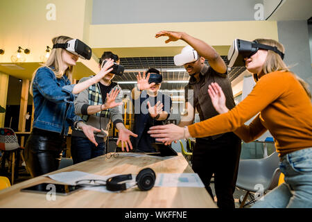 Young multiracial business People wearing virtual reality goggles with touching air during VR Meeting Conference at the office. Business men and women - Stock Photo