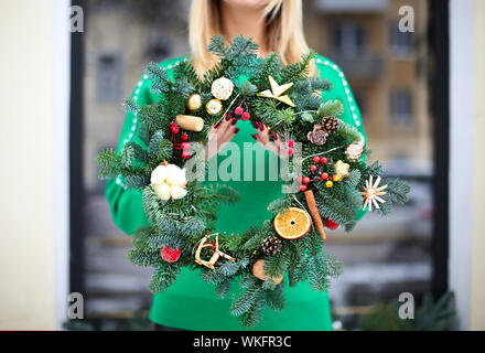 Girl holding Christmas wreath maked by herself outdoors. Christmas concept. Xmas mood - Stock Photo
