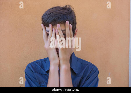 Portrait Of Teenage Boy Covering Face With Hands While Standing Against Wall - Stock Photo