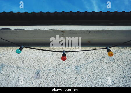 Low Angle View Of Colorful String Lights Hanging By Wall - Stock Photo